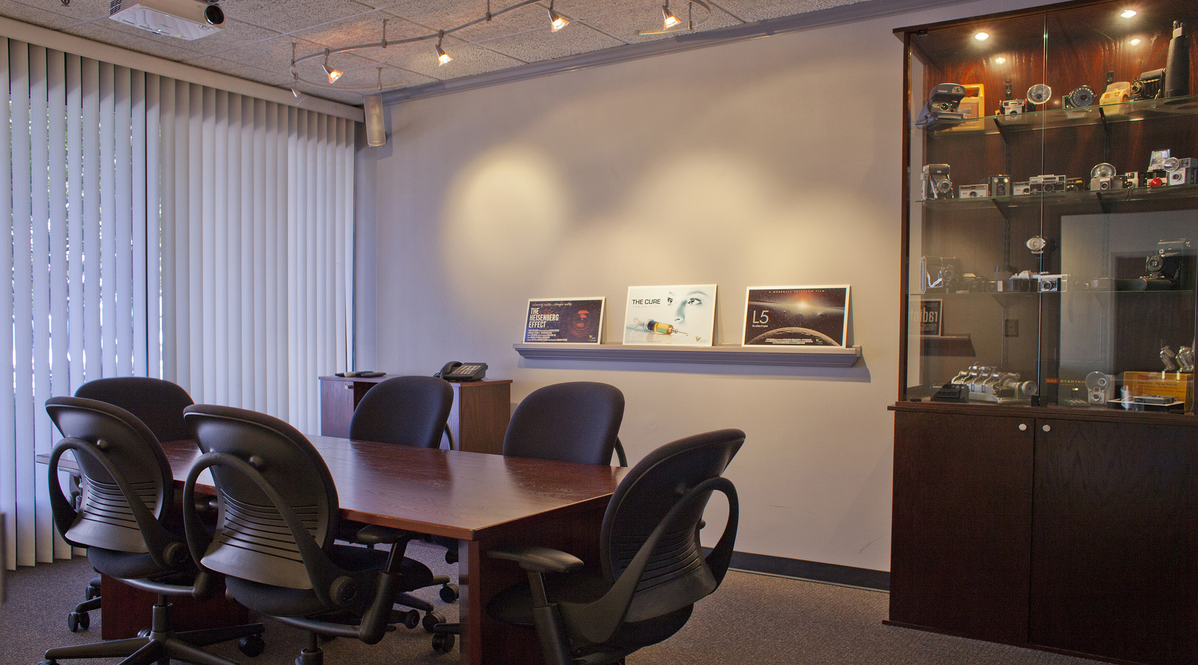 """This is our conference room. It has a table, indirect lighting, some comfortable Steelcase Leap chairs, a museum of unusual and vintage cameras, HD projection to a 90"""" screen and big windows that look out to the parking lot. We also have skinny shelves to display storyboards. It's a conference room."""