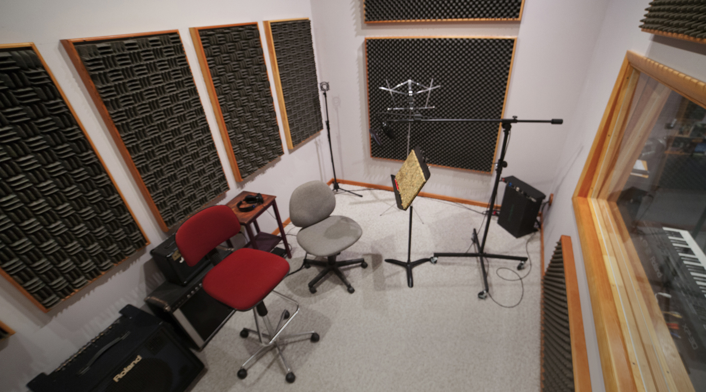 """Our recording room is far larger than a typical narration booth, and far more comfortable. Custom built as a room-within-a-room-within-a-room, it's dead quiet, and big enough for a string quartet or a very large drum kit. It's tunable - the Sonex® panels on the wall are removable so we can get just the right brightness, and we also have Sonex partitions that can separate performers so they can work together but be recorded cleanly on separate tracks. The booth is also fitted with custom-built silent ventilation, so the air conditioning or heating can keep the room at just the right temperature, even while recording. We weren't kidding about """"comfortable""""."""