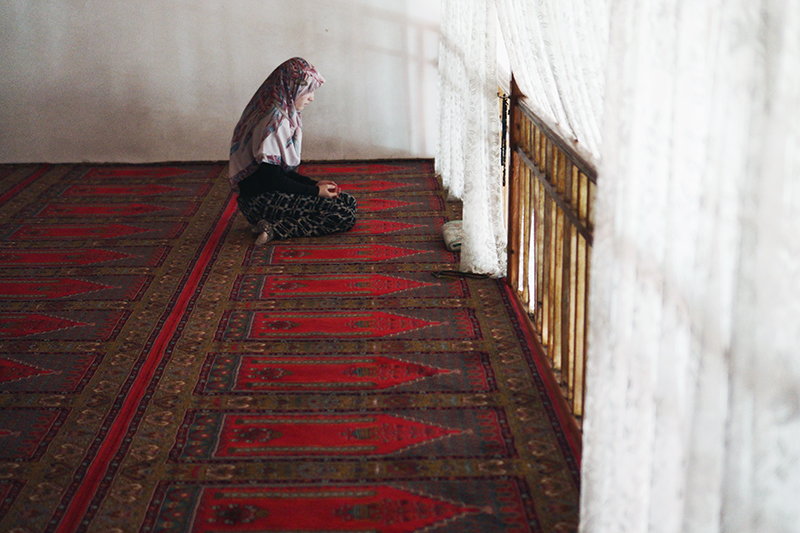 A young woman praying at the historic Arslanhane Mosque in Ankara.