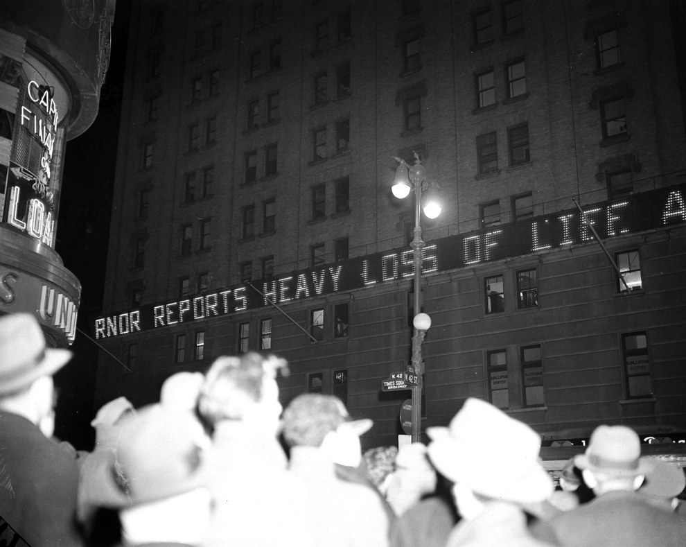 This is the scene in New York's Times Square early in the evening on December 7th, 1941, as crowds gather to read the news bulletins flashed on the electric bulletin board of the New York Times building..jpg