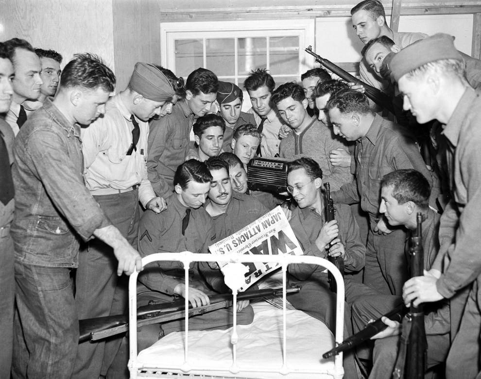 U.S. soldiers in San Francisco gather around the bed of one of their comrades to read the news of the bombing of Pearl Harbor..jpg