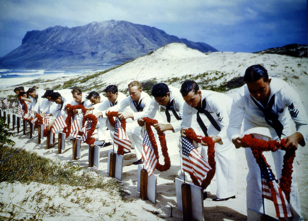 Uniformed American sailors place leis over the graves of their brothers in arms, in Spring 1942..jpg