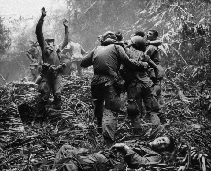 As fellow troopers aid wounded comrades, the first sergeant of A Company, 101st Airborne Division, guides a medevac helicopter through the jungle foliage to pick up casualties suffered during a five-day patrol near Hue in Vietnam in April 1968..jpg