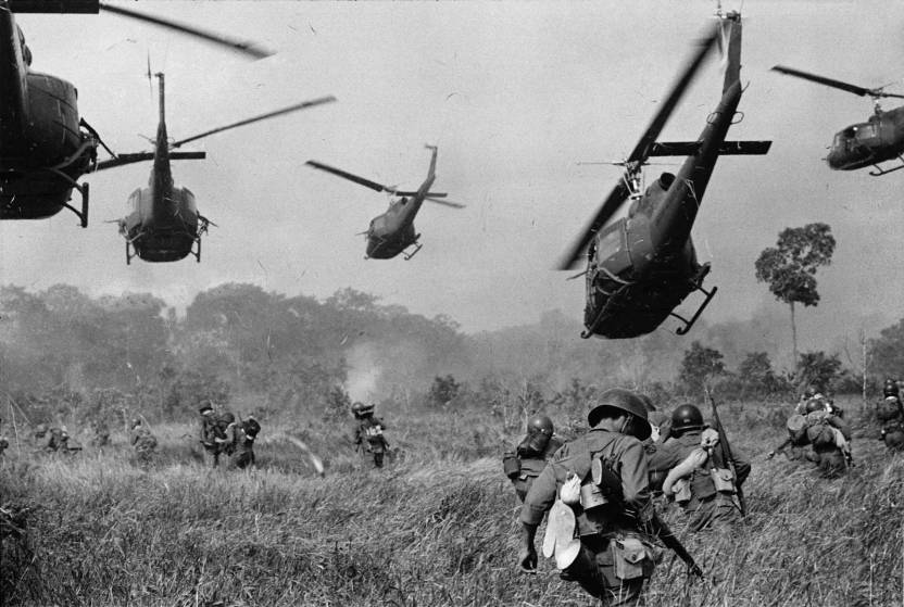 Hovering U.S. Army helicopters pour machine gun fire into the tree line to cover the advance of South Vietnamese ground troops in an attack on a Viet Cong camp 18 miles north of Tay Ninh, northwest of Saigon near the Cambodian border, in March 1965..jpg