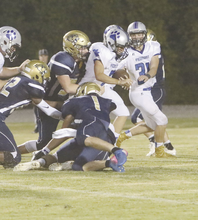 The Lions' Alex Noblett (1) takes down a Cougar runner with a little help from his friends on defense.