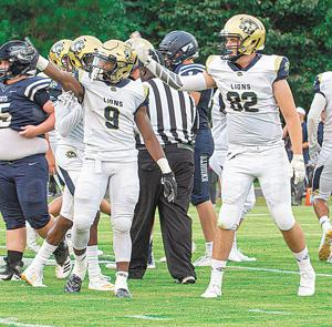 Keon McGhee (9) and Russell Brown (82) signal a Loganville Christian first down during the Lions' victory over Bethlehem Christian on Friday night.