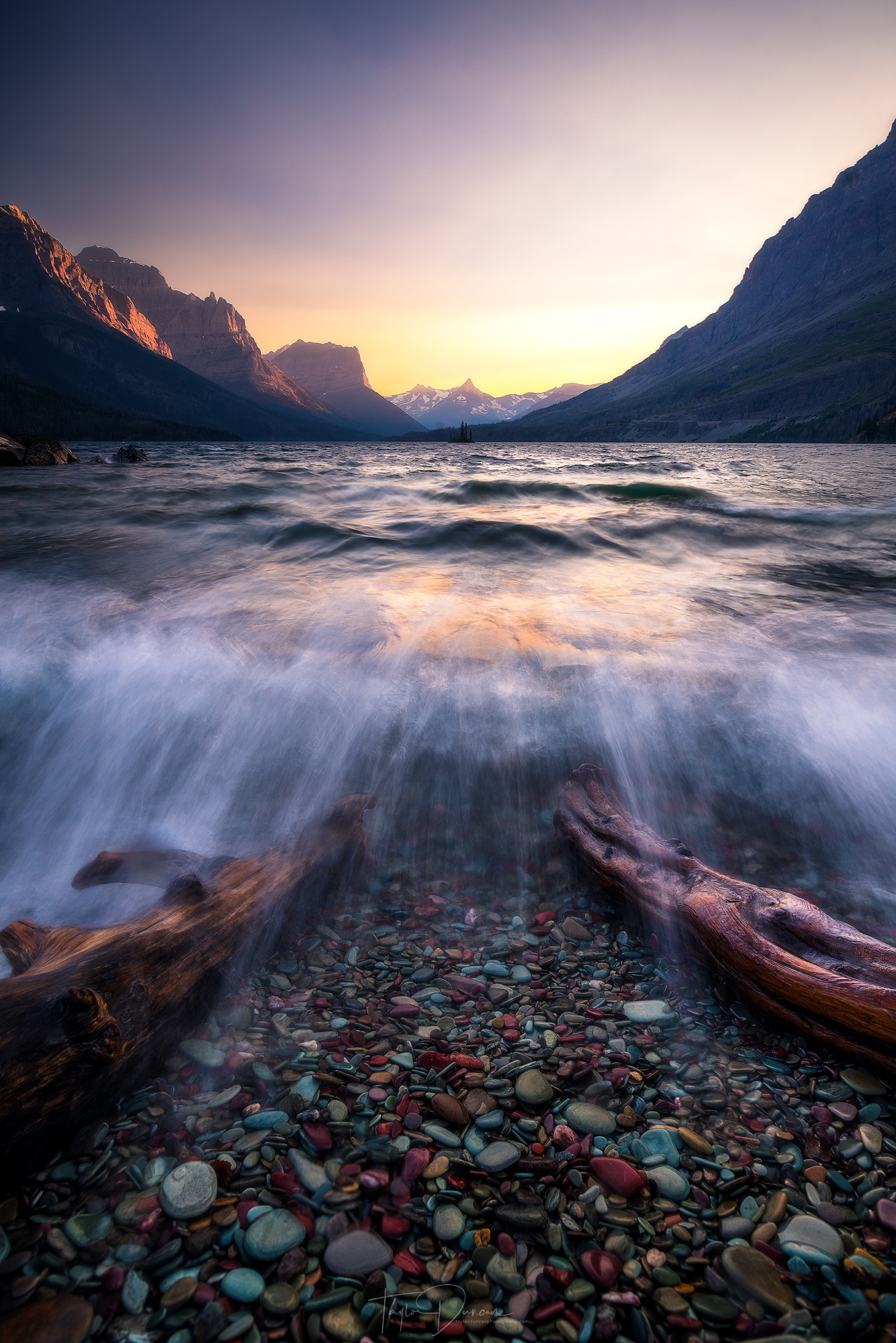 St. Mary Lake churns out waves along the lakeshore under a fiery sunset