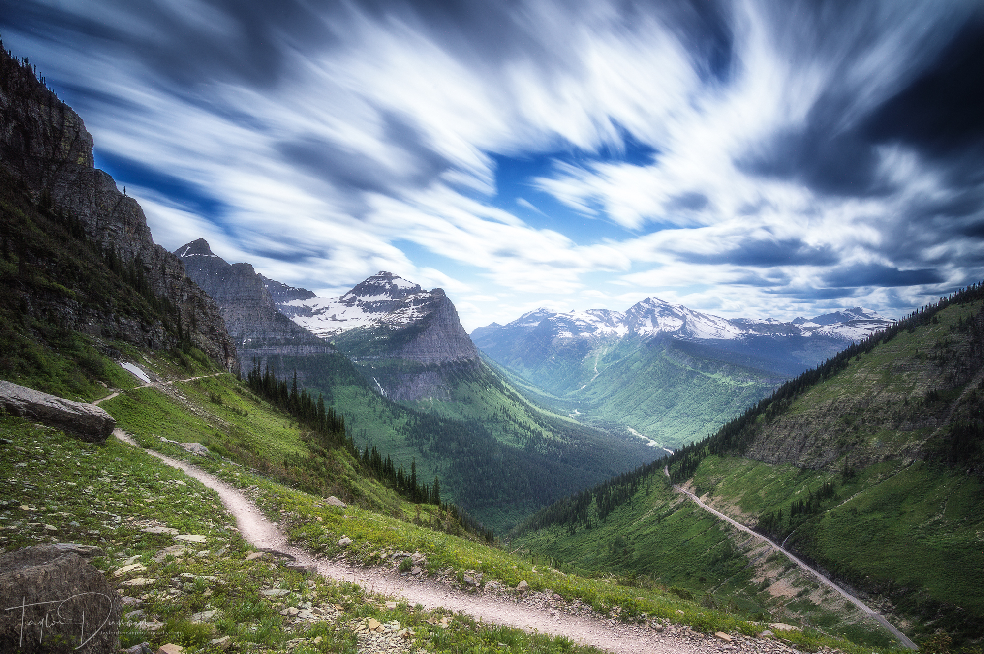 Clouds roll across the sky above the Highline Trail with the Going-to-the-Sun Road below