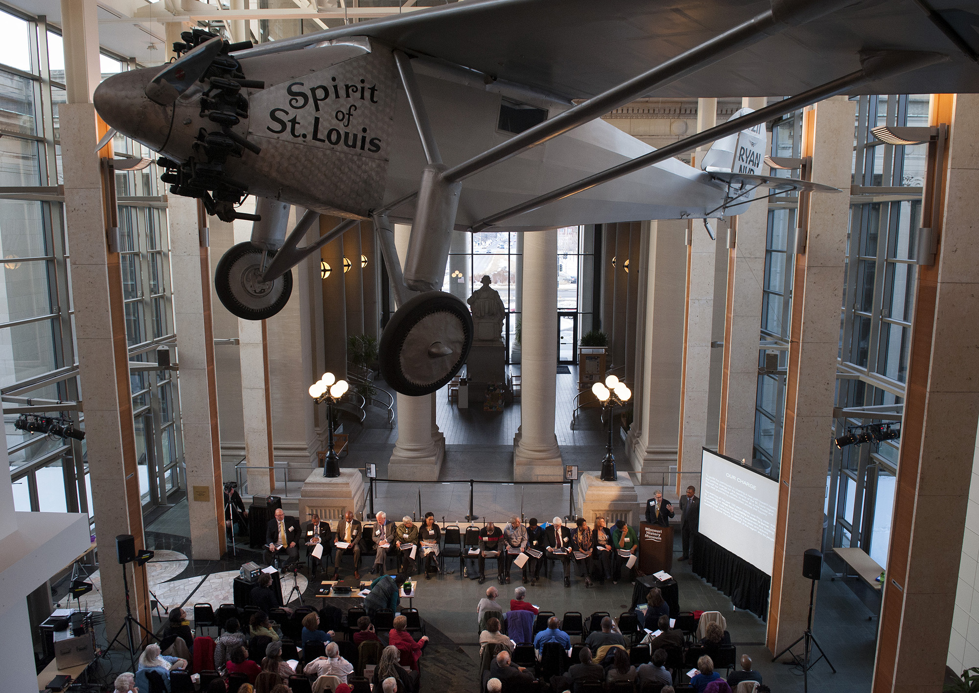 "Members of the Ferguson Commission appointed by Missouri Gov. Jay Nixon gather beneath the reproduction of Charles Lindbergh's ""Spirit of St. Louis"" at the Missouri History Museum in Forest Park in St. Louis for their meeting Monday, March 2, 2015. It was the group's seventh meeting. Photo © copyright 2015 Sid Hastings."
