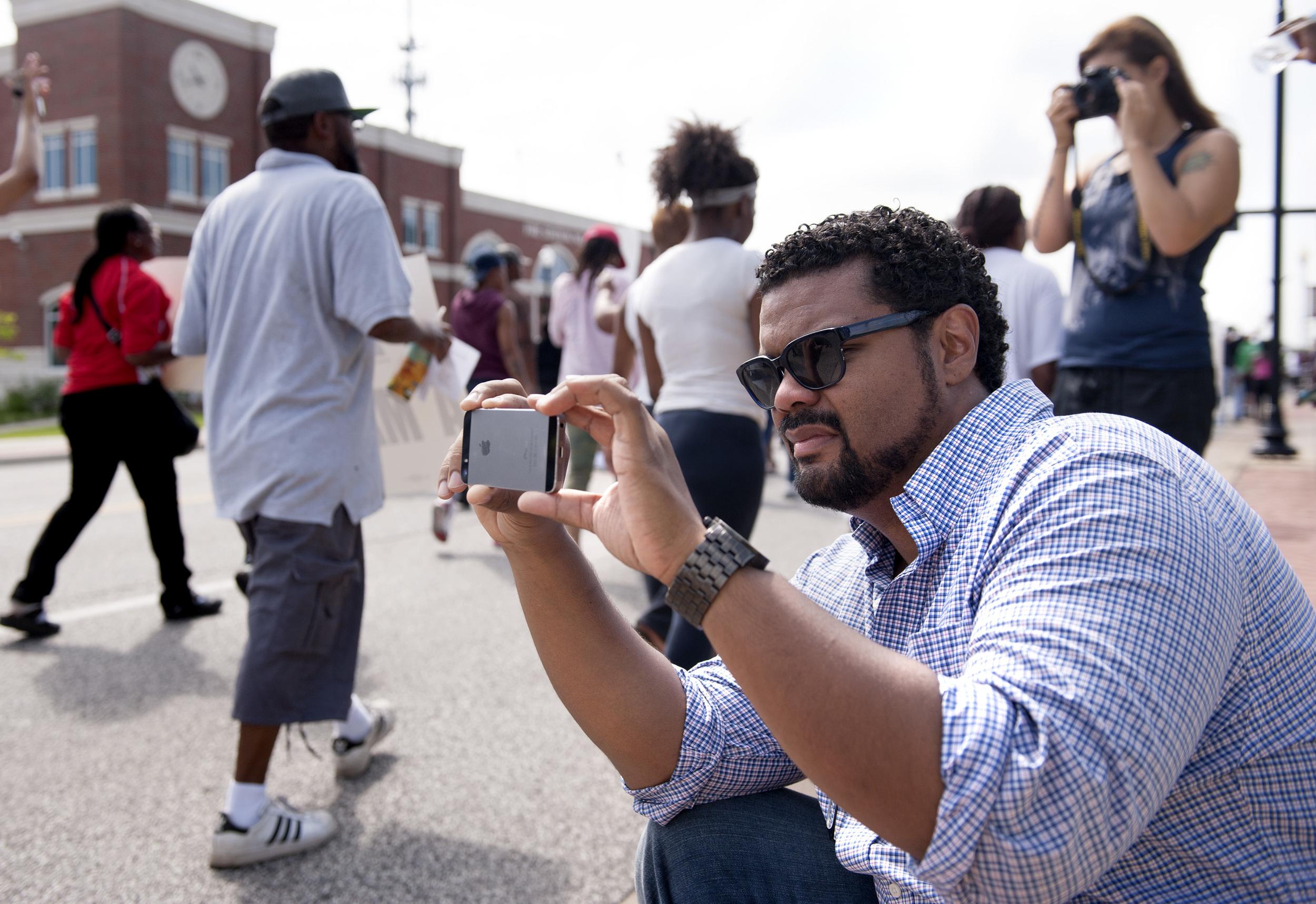 St. Louis Alderman Antonio French, 21st Ward, photographs protestors marching along Florissant Road in downtown Ferguson, Mo. Monday, Aug. 11, 2014. The group marched along the closed street, rallying in front of the town's police headquarters to protest the shooting of 18-year-old Michael Brown by Ferguson police officers. Brown, who was killed in a confrontation with police in the St. Louis suburb, was shot Saturday, Aug. 9, 2014, and died following the confrontation with police. (AP Photo/Sid Hastings)