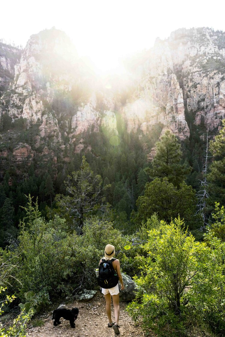 Magical Sun burst over the cliffs of Oak Creek Canyon being watched by a girl and her dog on Cookstove Trail in Sedona