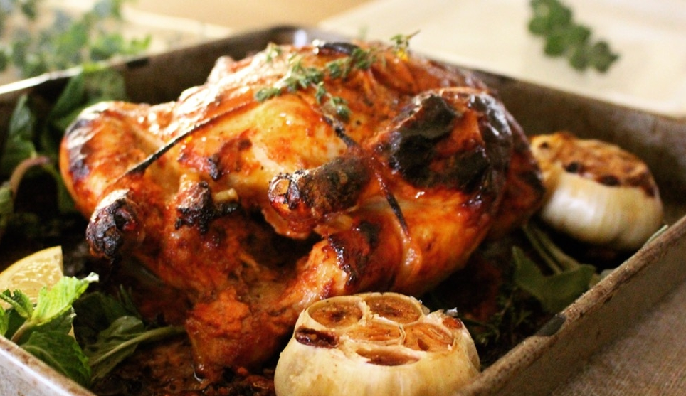 Whole Roasted Chicken Tikka Masala     Ingredients:   1 4-5 LB whole, organic chicken   1 head garlic   1 meyer lemon  1/2 cup of greek yoghurt   3 T olive oil   1/2 t coriander  1/2 t cumin  1 t paprika  1 t garlic powder   1/2 t garam masala   1/2 t chili powder   Salt & Pepper   Preheat oven to 375 degrees. Before trussing the chicken season generously with salt and pepper on the outside and inside of the bird. Make your marinade- Mix half a cup of greek yoghurt, coriander, cumin, paprika, garlic powder, garam masala, chili powder and juice of 1/2 lemon. whisk until smooth and the spices have blended evenly with the yoghurt. Coat the cavity and outside of the bird evenly. Truss your chicken and place in a roasting pan.   Watch a video on how to truss here:  https://www.marthastewart.com/973737/how-truss-chicken    Cut garlic head in half and place on opposite sides of the board. Drizzle with olive oil and cook covered for 1 hour and uncovered for the last 1/2 hour. Serve w/ crispy potatoes or turmeric rice and mixed green salad.