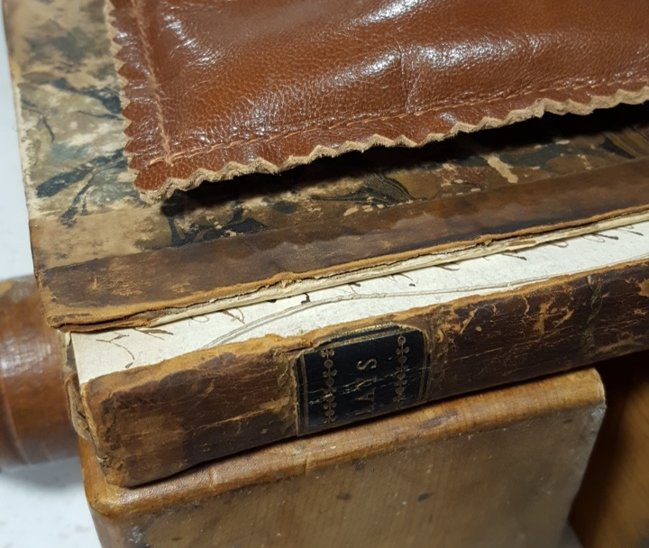 Preparing to reattach the covers of a half-leather book.