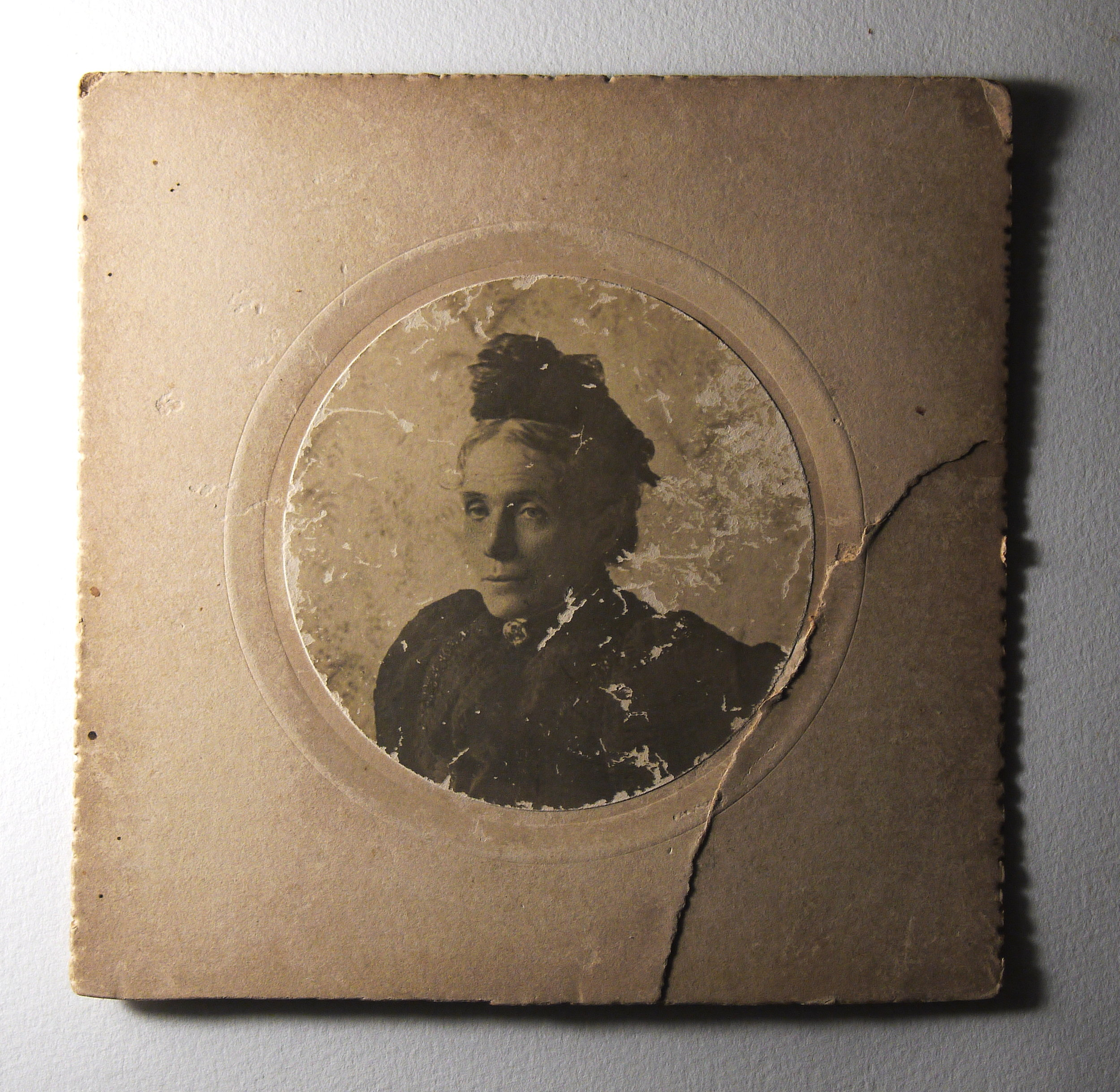 Antique family photograph, with damage to the board and photographic emulsion.
