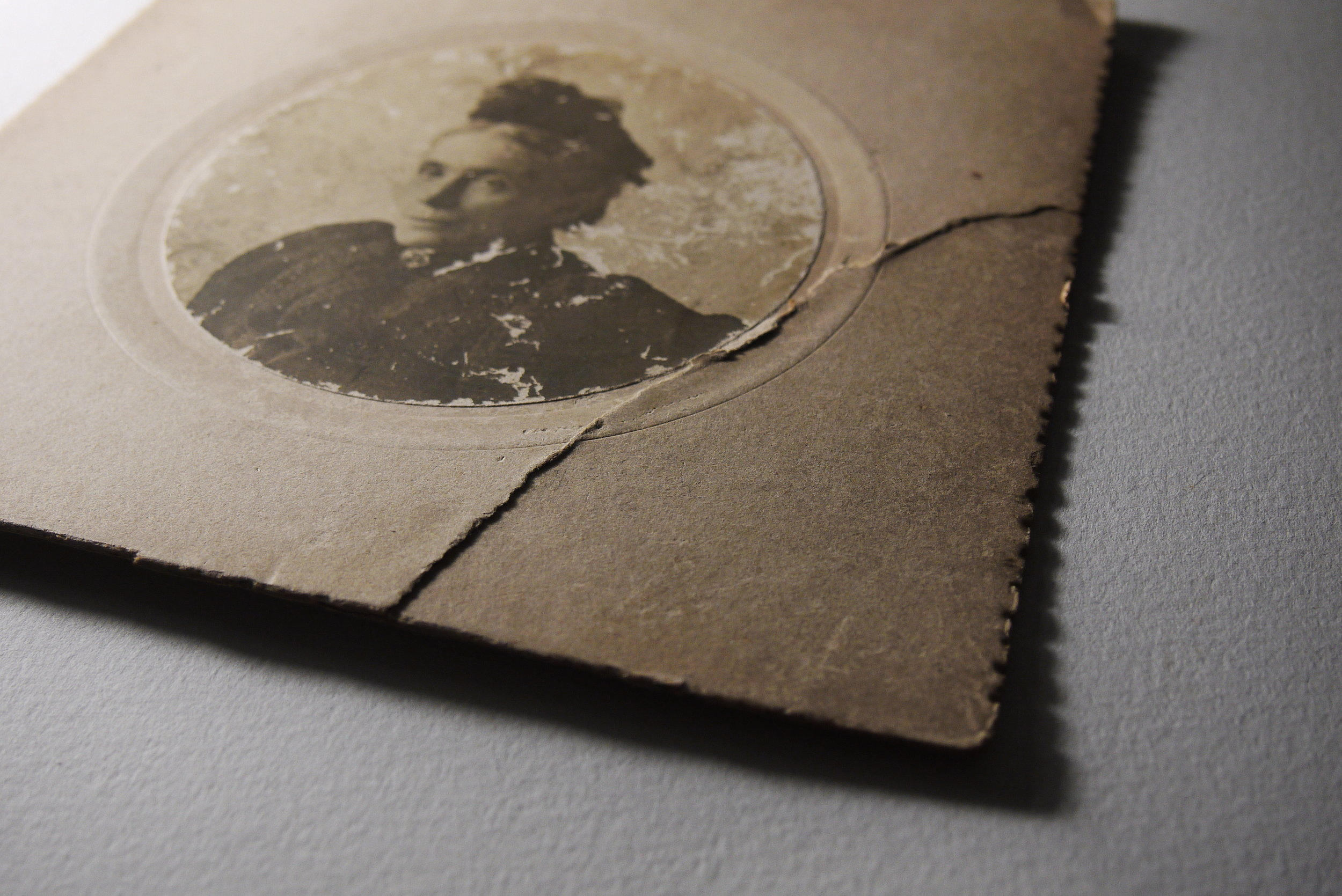 Damaged antique photograph in raking light.
