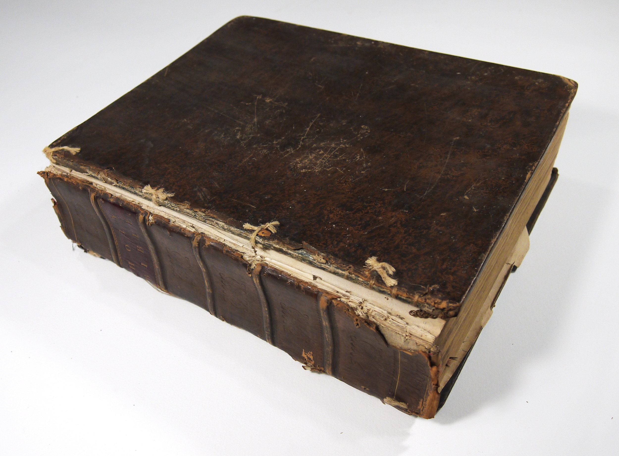 The family bible in damaged condition - boards are off, joints are ragged, and previous repairs have punctured the covers.