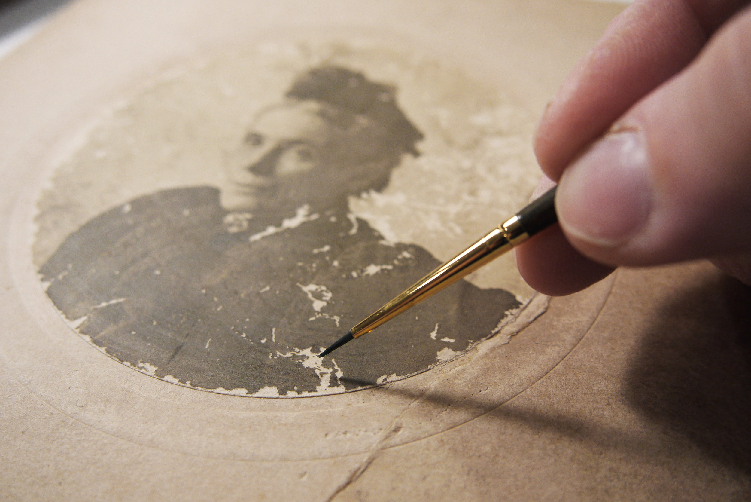 Applying watercolour to the lost emulsion of the photograph.