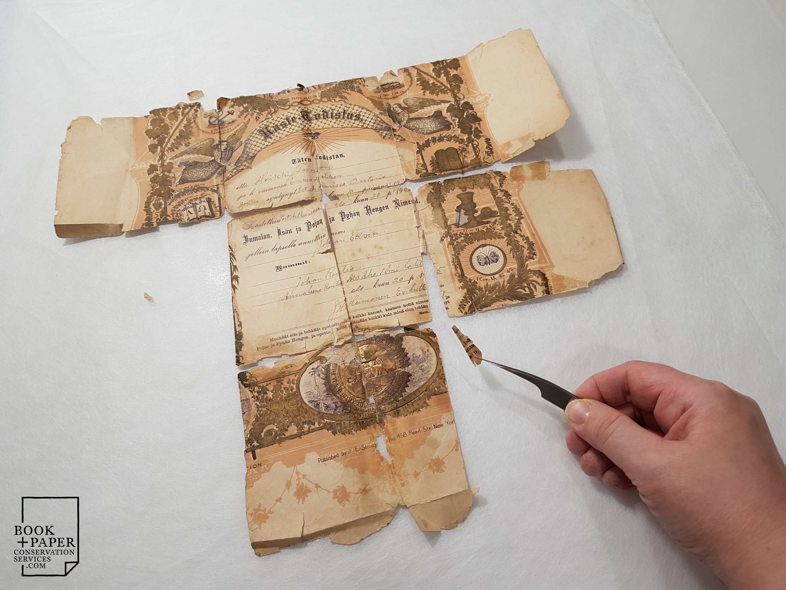 Reassembling fragments of the birth certificate before repair by lining.