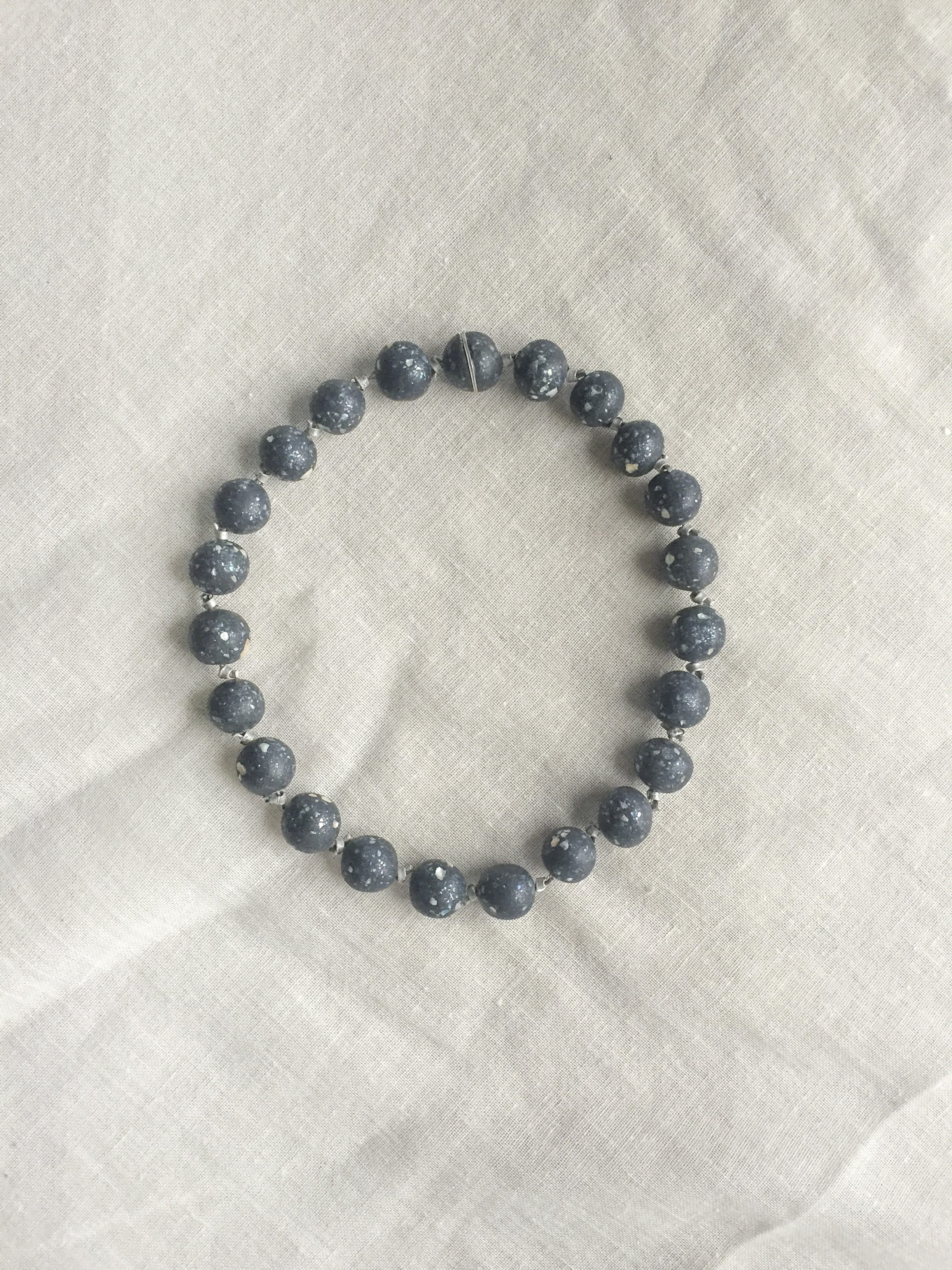 Black bead necklace - Tying the cosmos together[read more: encapsulating the universe in a bead]