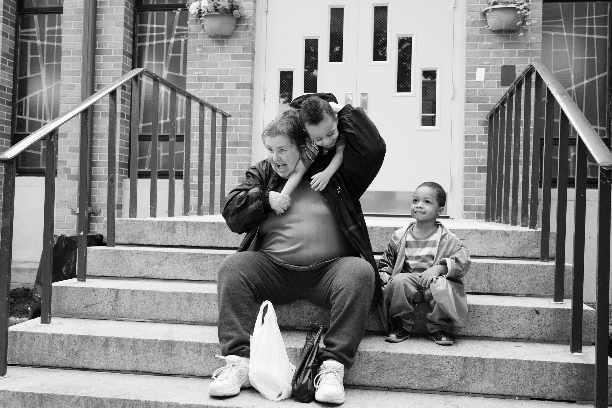 Carol, 65, who served 35 years, one year after her release with Darjay and her honorary grandchild Cecil (right), both almost three years old. Long Island City, NY (2014)