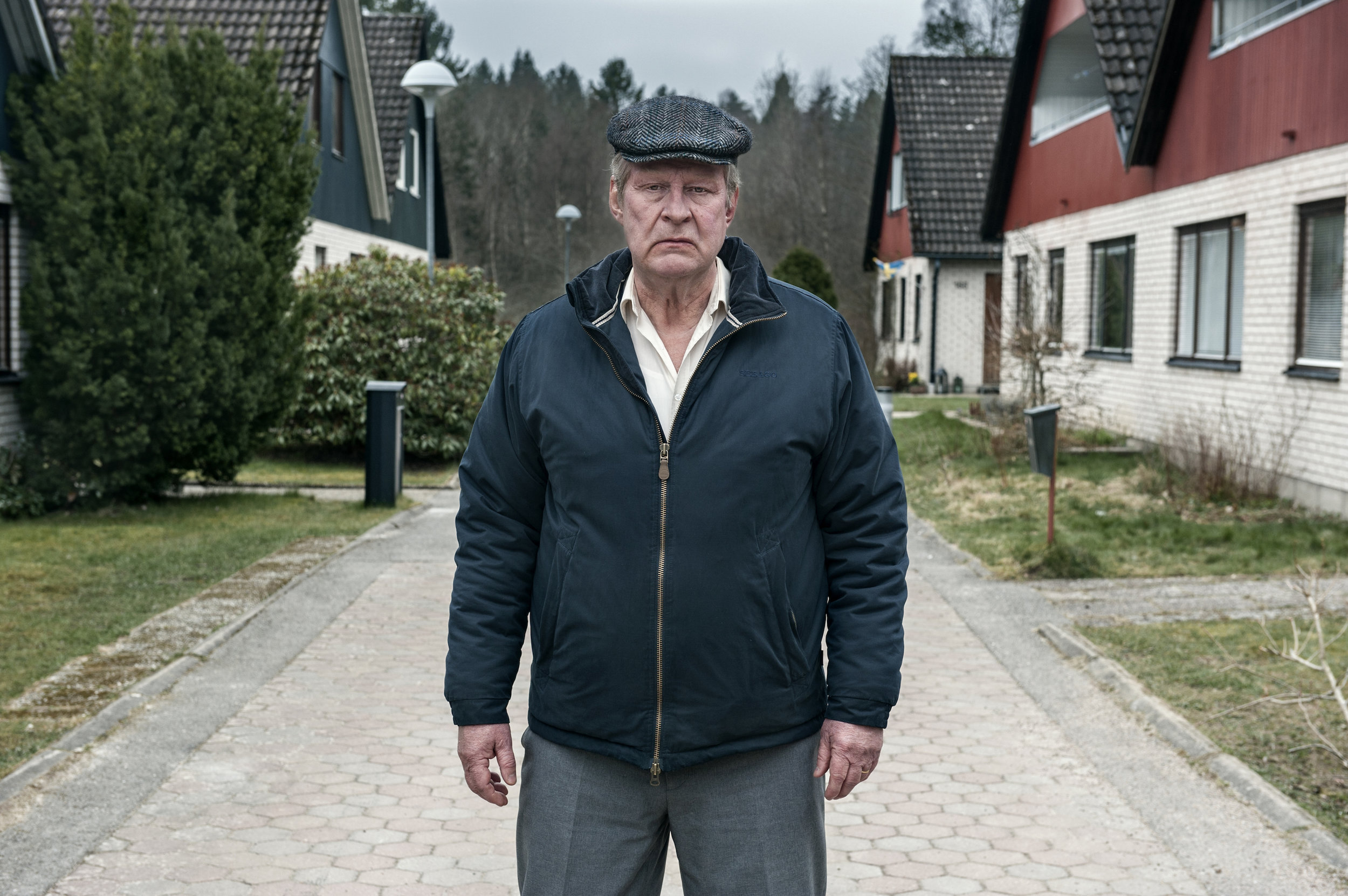 A bitter Ove (Rolf Lassgård) stands in the middle of the gated community pathway where cars are prohibited.