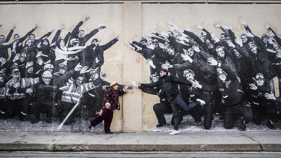 Varda and JR pose in front of one of their murals.
