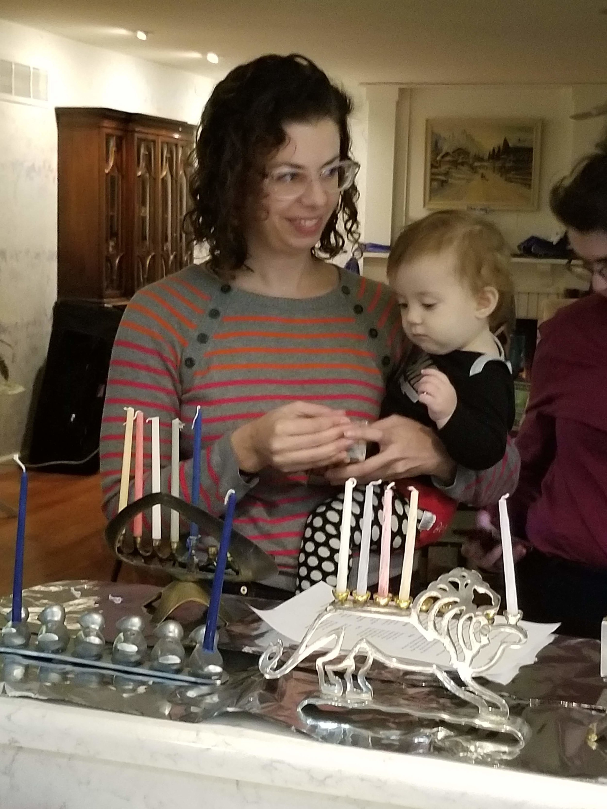 Deborah Spivak and daughter Eleanor light their Hanukiah.jpg