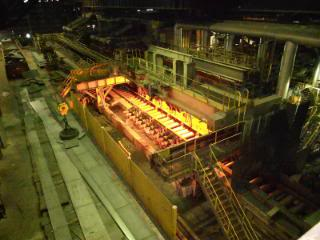 """""""Walking Beam Furnace. Door is opening getting ready to extract a hot slab. Crane with magnet is picking up pieces of a cobble on the cobble burn rack."""""""