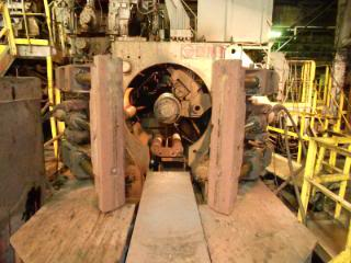 """""""Looking into #3 Super Coiler looking through the 'Upender'into the mandrel and assemblies of the coiler. Apparatus on the bottom with 2 rolls is the 'Stripper Car'that removes the coil from inside the coiler to the Upender."""""""