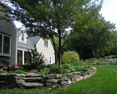 Stone retaining wall for raised planting bed and stone steps