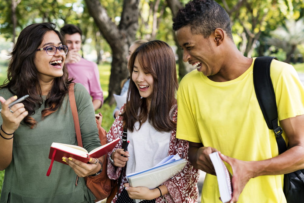 A Freshman's Crash Course - freshmen in college laughing and talking with books