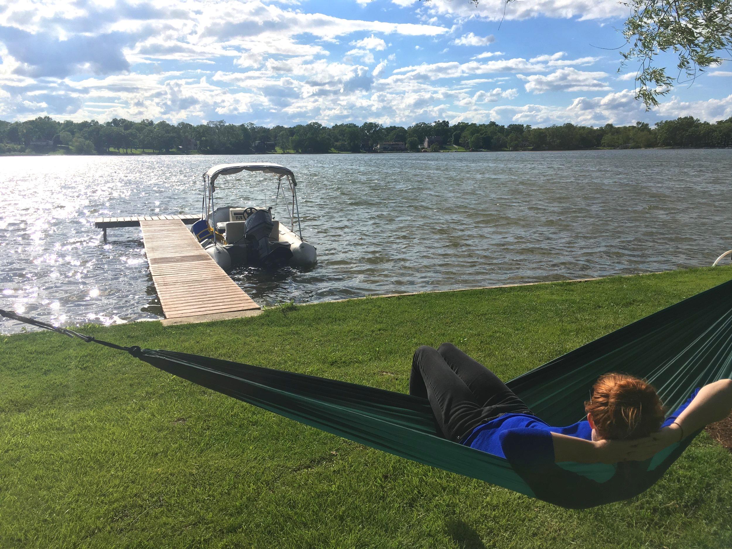 girl relaxing in hammock at lake