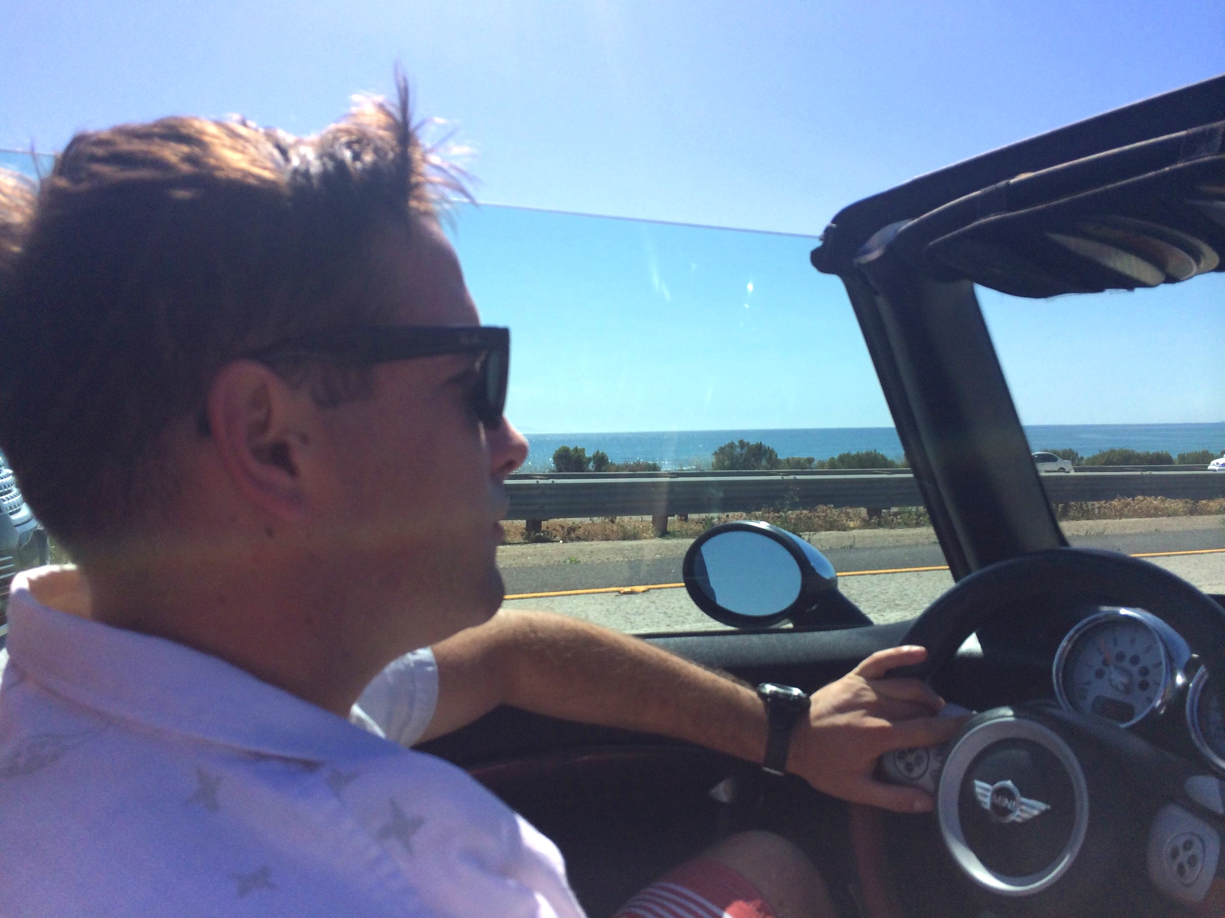 man driving in convertible by beach