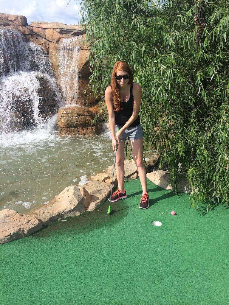 girl playing mini golf in front of waterfall