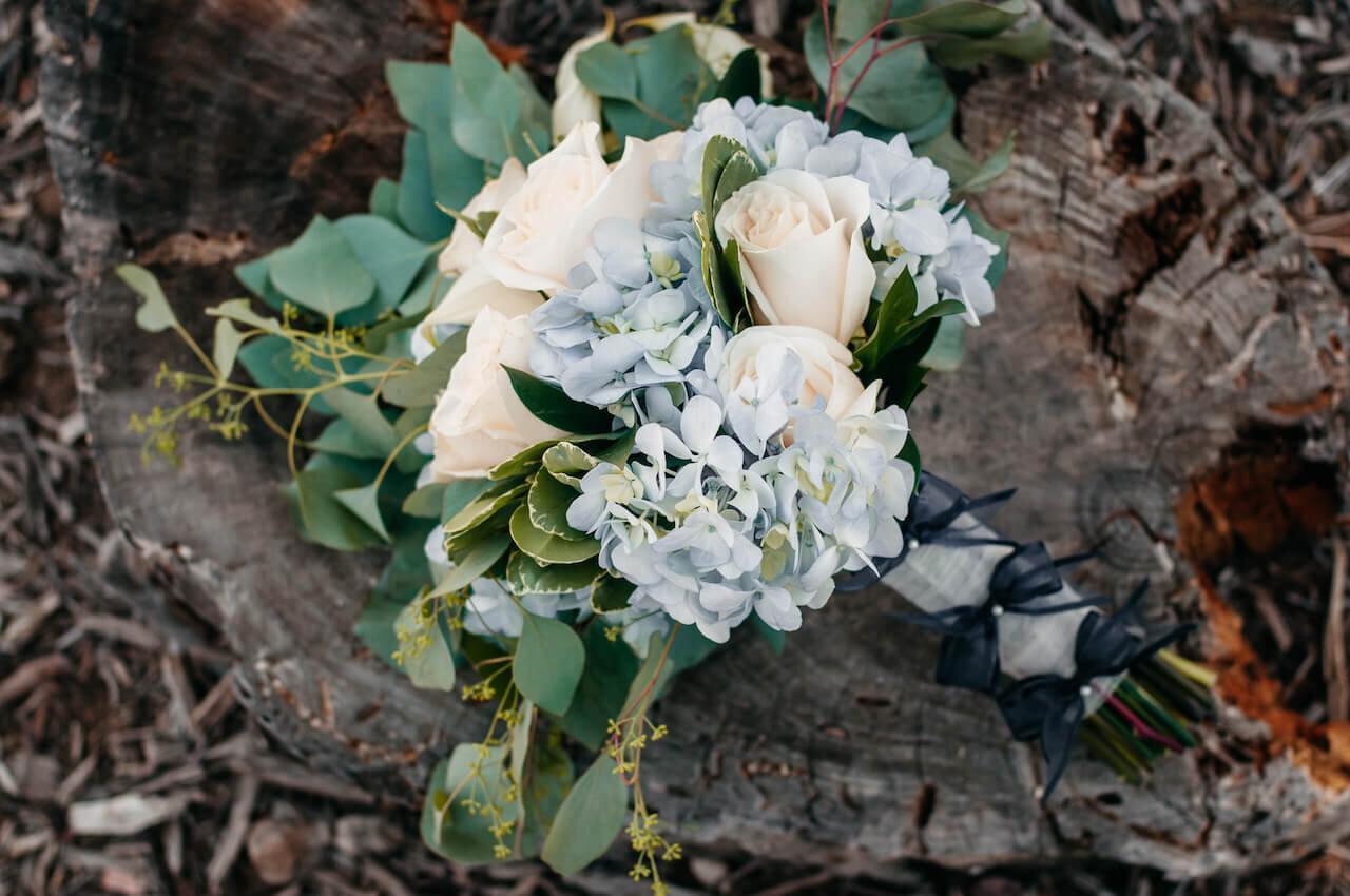 wedding bouquet with ribbon on tree stump