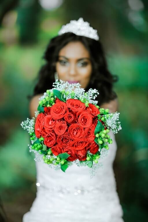 bride holding bouquet of roses in front before her bouquet toss