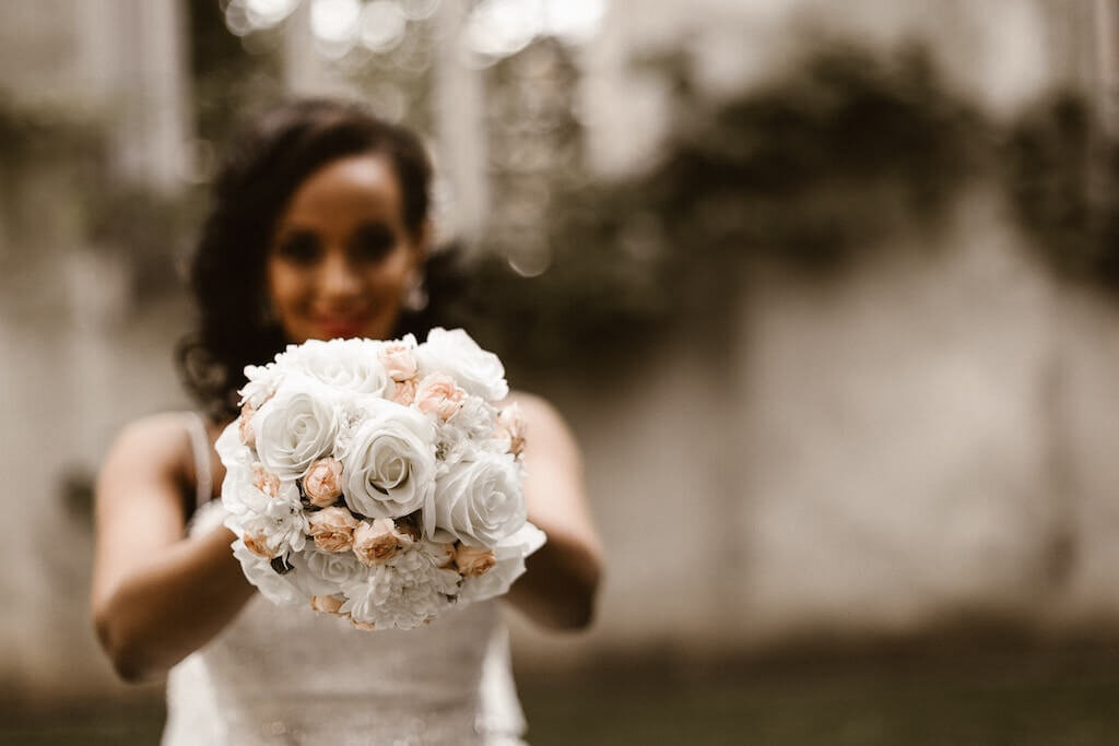 bride holding white rose bouquet in front of her, getting ready to toss it