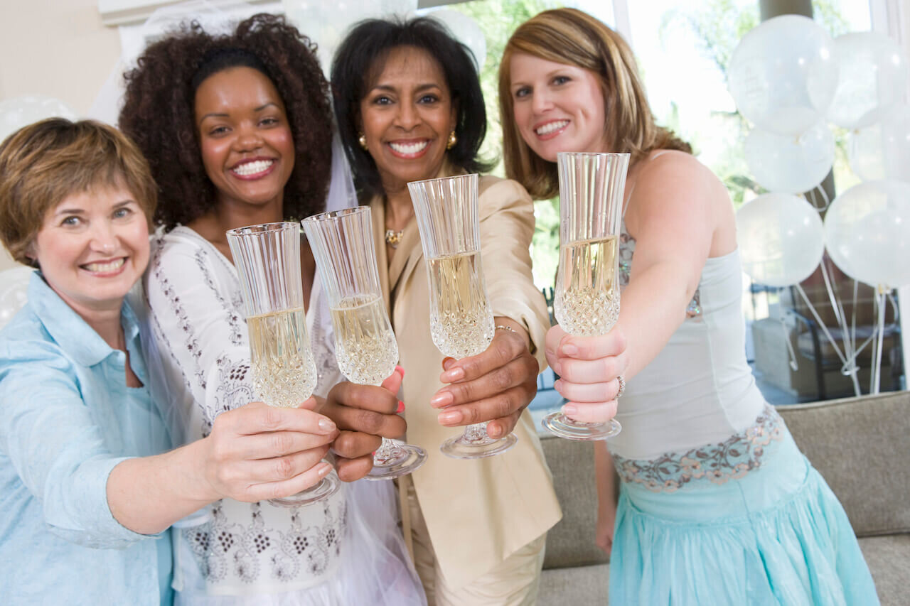 4 women holding champagne at a themed bridal shower
