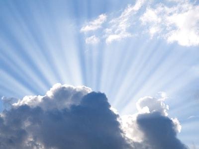 sun beams bursting behind cloud