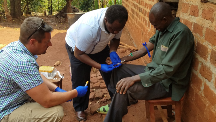 John Dye, left, and his team from the U.S. Army Medical Institute of Infectious Diseases at Fort Detrick took blood samples from Ebola survivors with the help of Ugandan researchers like Dr. Julius Lutwama, center, of the Uganda Virus Research Institute.