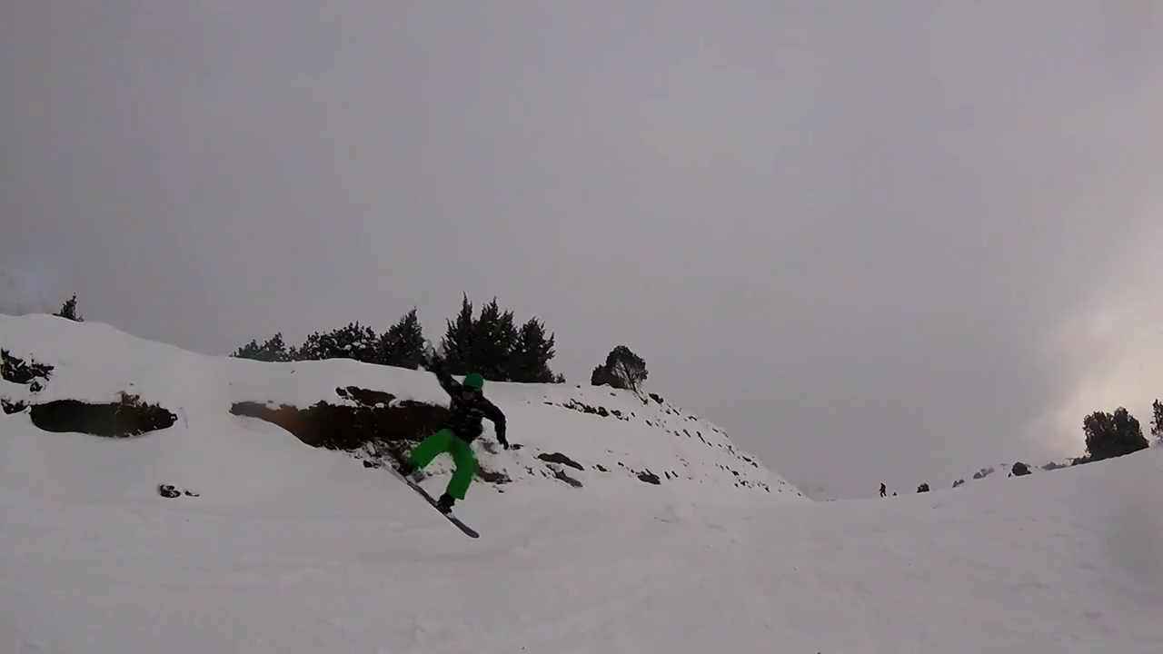 A snowboarder jumping from a small ramp.