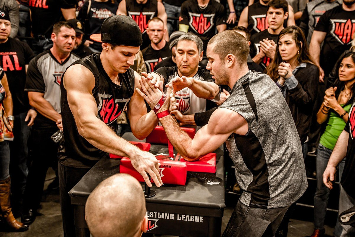 - Athletes compete standing at a special table. Their elbows are on the pads. The winner is the first to press the opponent's hand to the pad.