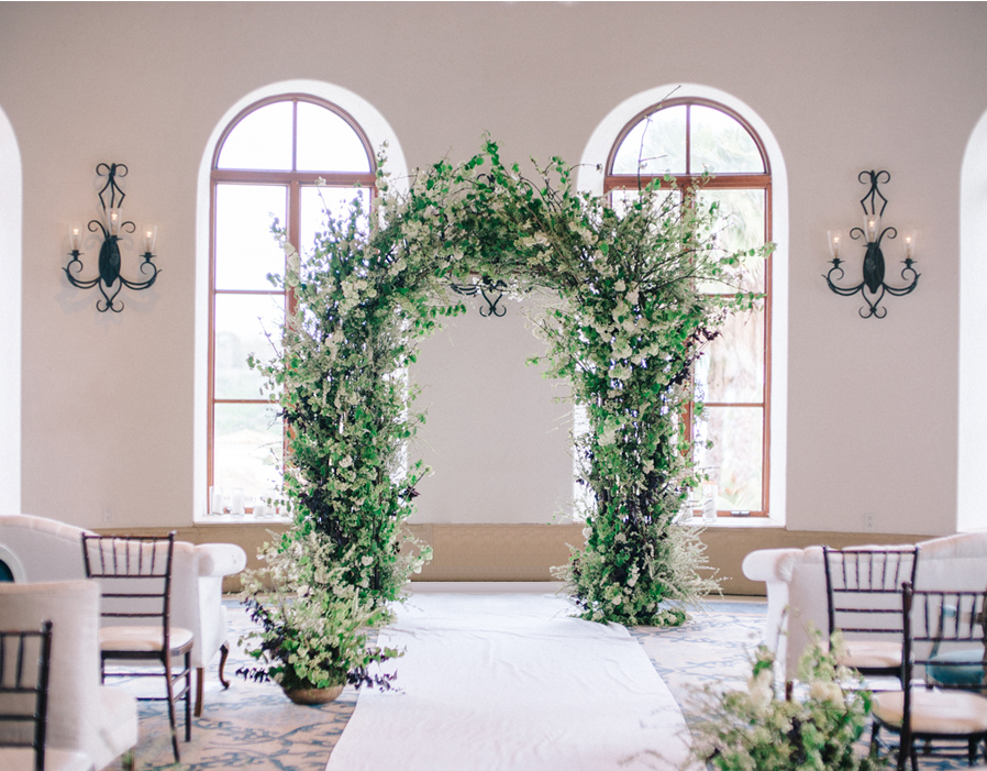 OUR CEREMONY RAIN PLAN BROUGHT US INDOORS BUT THIS WILD BLOSSOM BRANCH ARCH PROVIDED THE NATURAL BACKDROP THE COUPLE DREAMED OF. -
