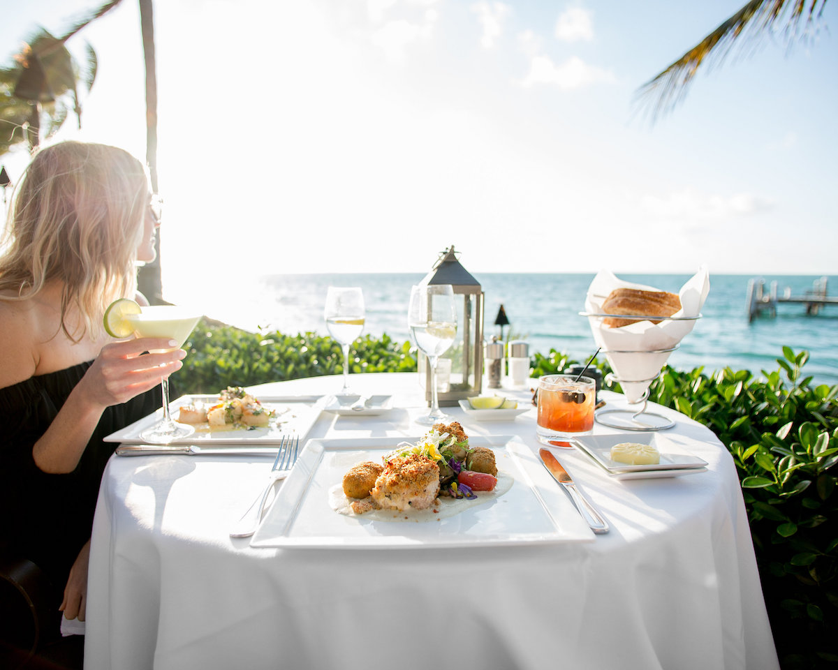 Girl holding drink at dinner overlooking water at sunset key cottages.jpg