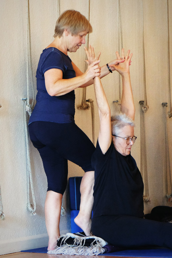 Adjusting a student in class at Adeline Yoga Studio