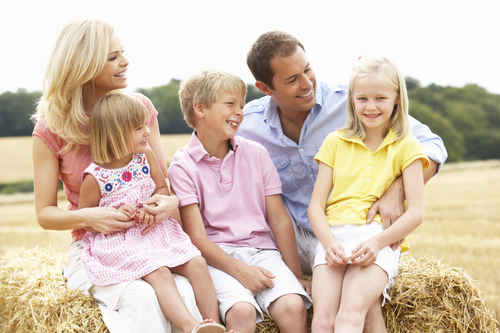smileing family with three kids - receive family dental services in mobile al