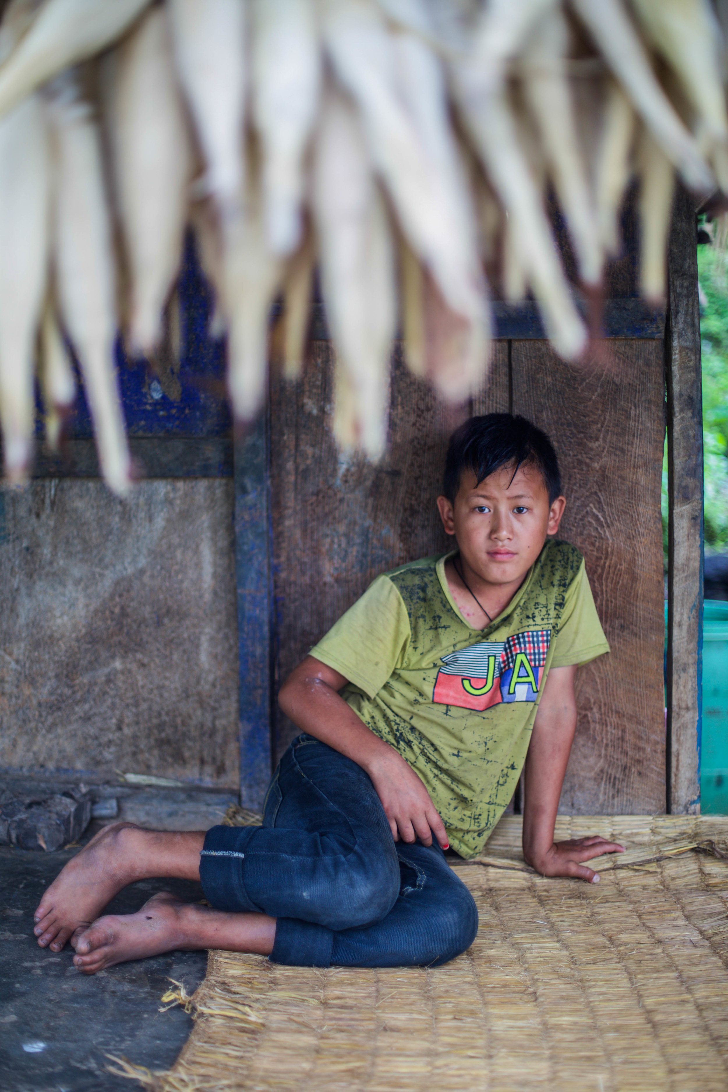 Sunil, 11, the only remaining child of Chari and Bhoj, sits outside their home on Aug. 1, 2016.