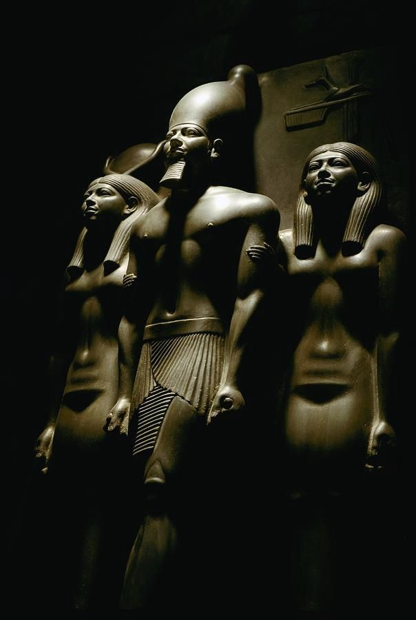 Pharaoh sandwiched between the goddess Hathor and patron god of Thebes