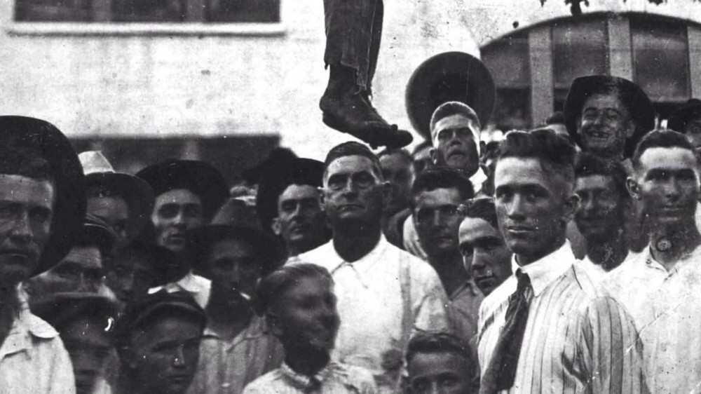 White civilians pose for the camera after lynching a black person.