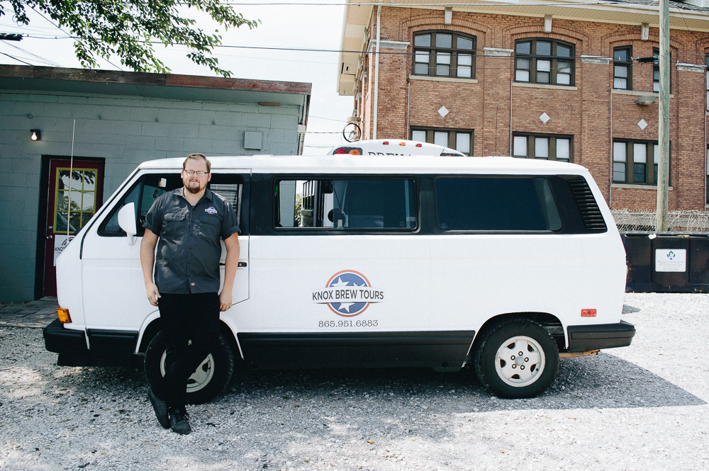 """Zack standing in front of his VW Bus, nicknamed """"Scruffy""""."""
